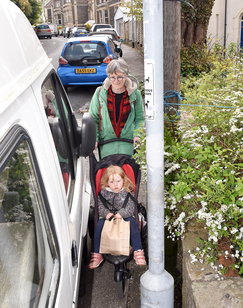 Vehicle parked on the pavement obstructs route for parent with pram.