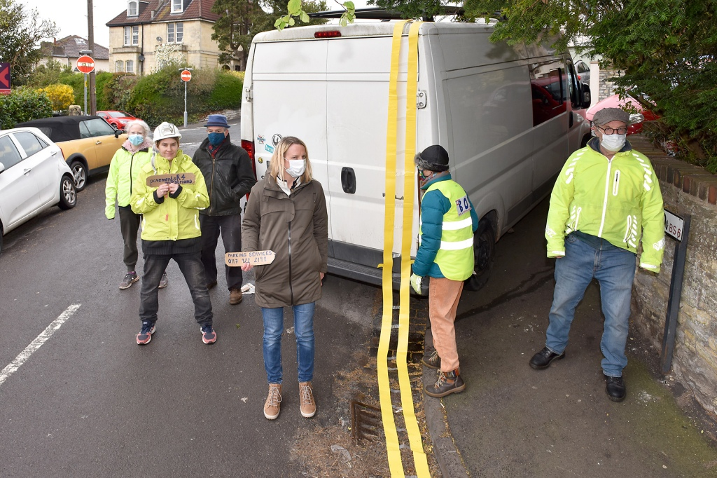 BOSA members drape yellow lines over illegally parked vehicles. Image shows a white van surrounded by BOSA members.