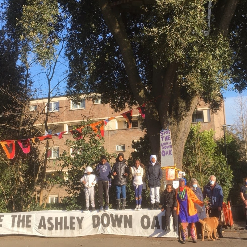 Community standing by the Ashley Down Oak with banner.