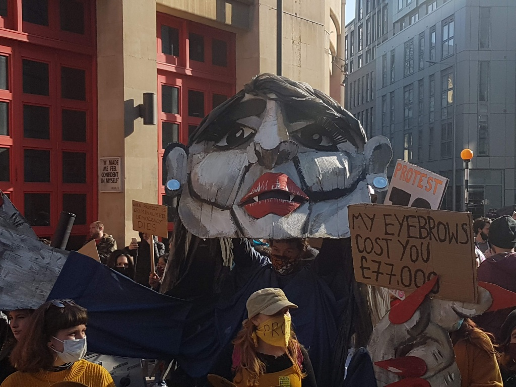 Image from Kill the Bill on April 3rd, showing a protester dressed as Priti Patel, with a giant cardboard head.
