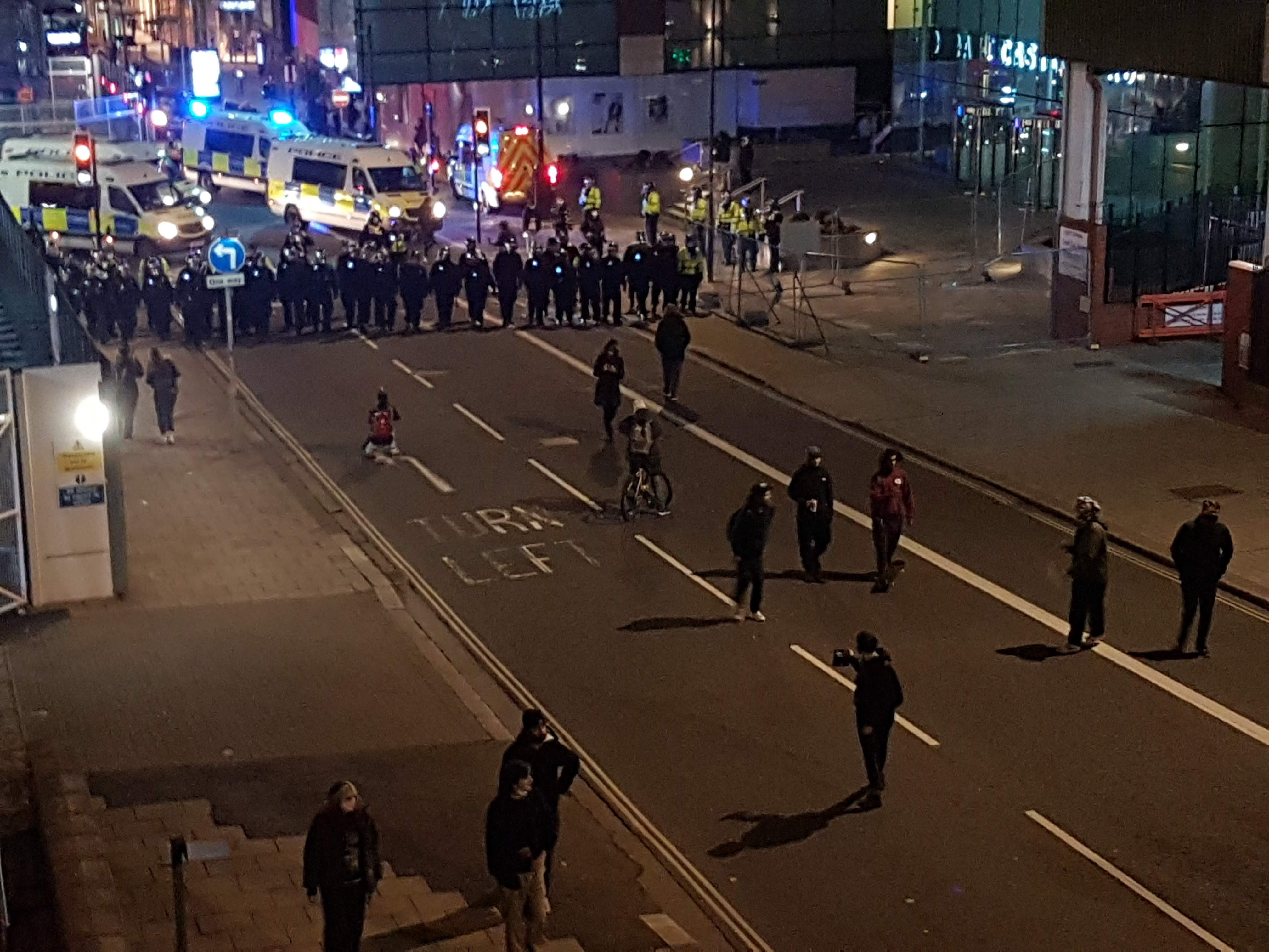 Around 15 protesters walk away from 40 riot police