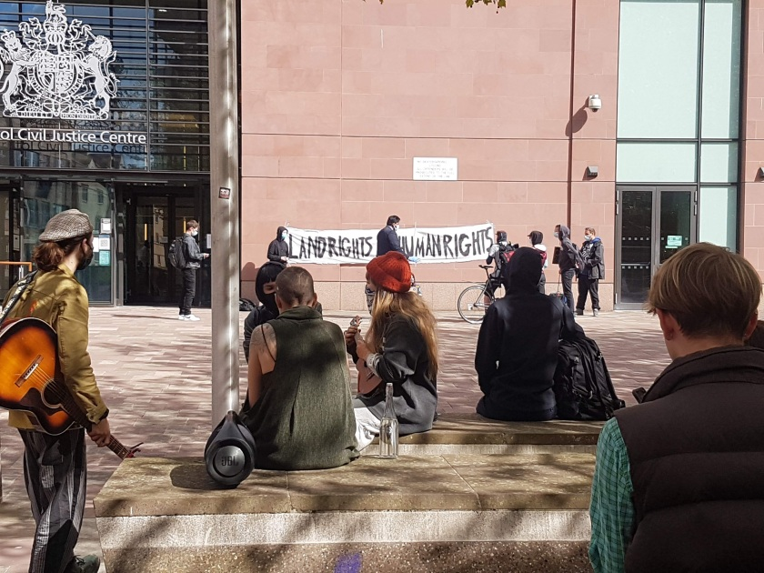 """11 Supporters outside the courthouse. Two in the foreground are playing guitars. In the background a banner reads """"land rights are human rights"""""""