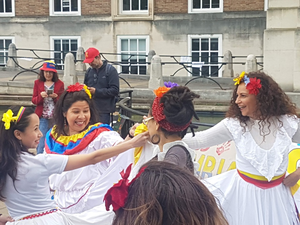 Four women dressed in white dresses hold one hand in the centre of the circle as they dance around the edge