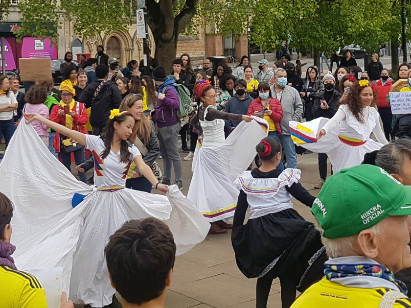three dancers in white dresses whilst a crowd watches