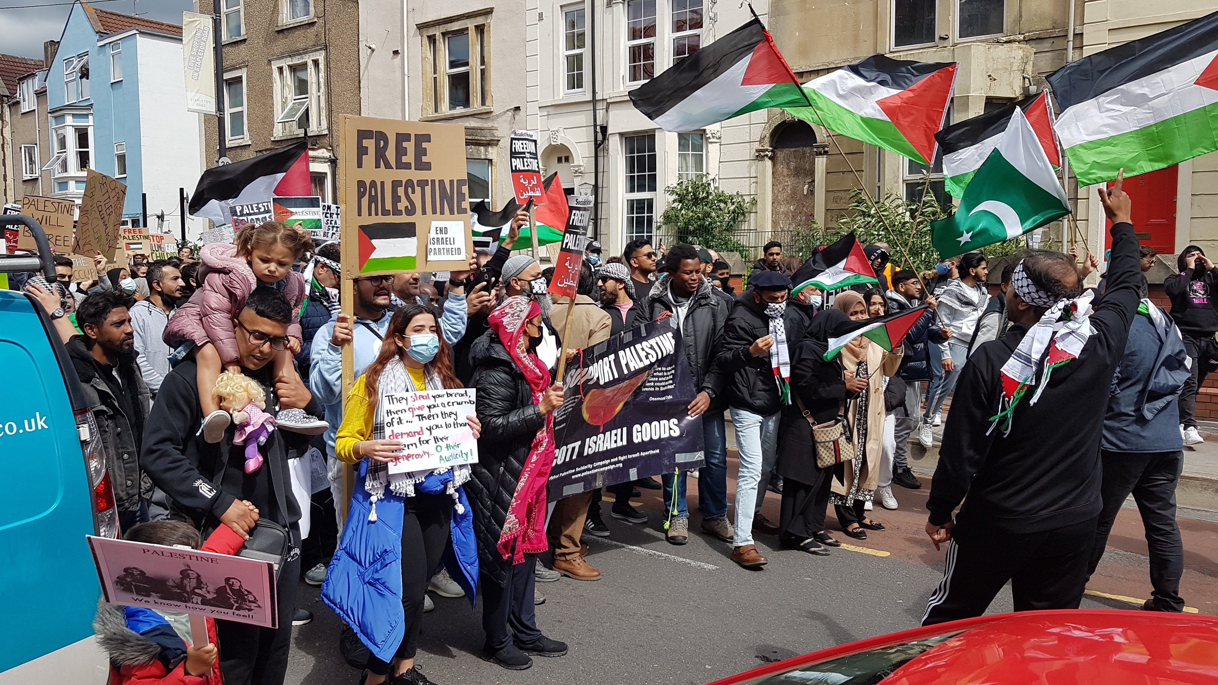 """Large crowd gather behind a banner that reads """"support Palestine. Boycott Israeli goods"""""""
