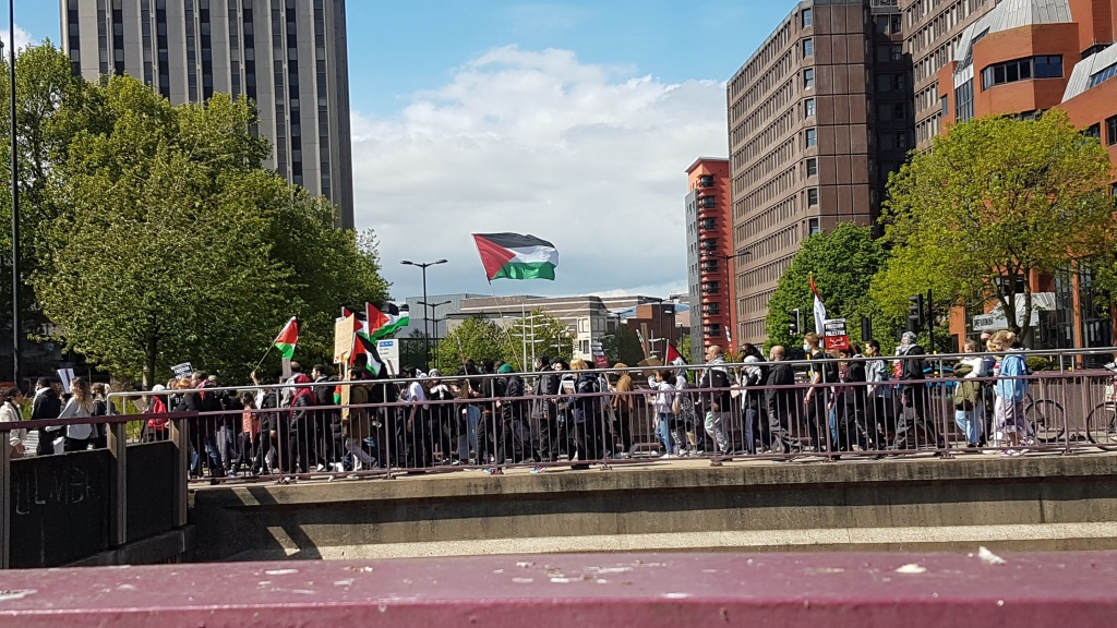 Protesters crossing a foot bridge waving Palestinian flags. the sky in the background is blue.
