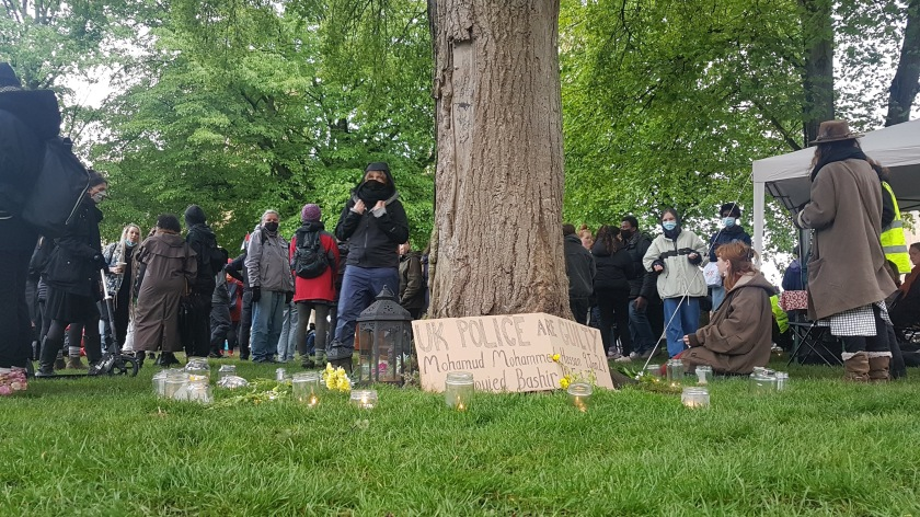 """Tree surrounded by candles and flowers and a sign that reads """"UK Police are guilty"""""""