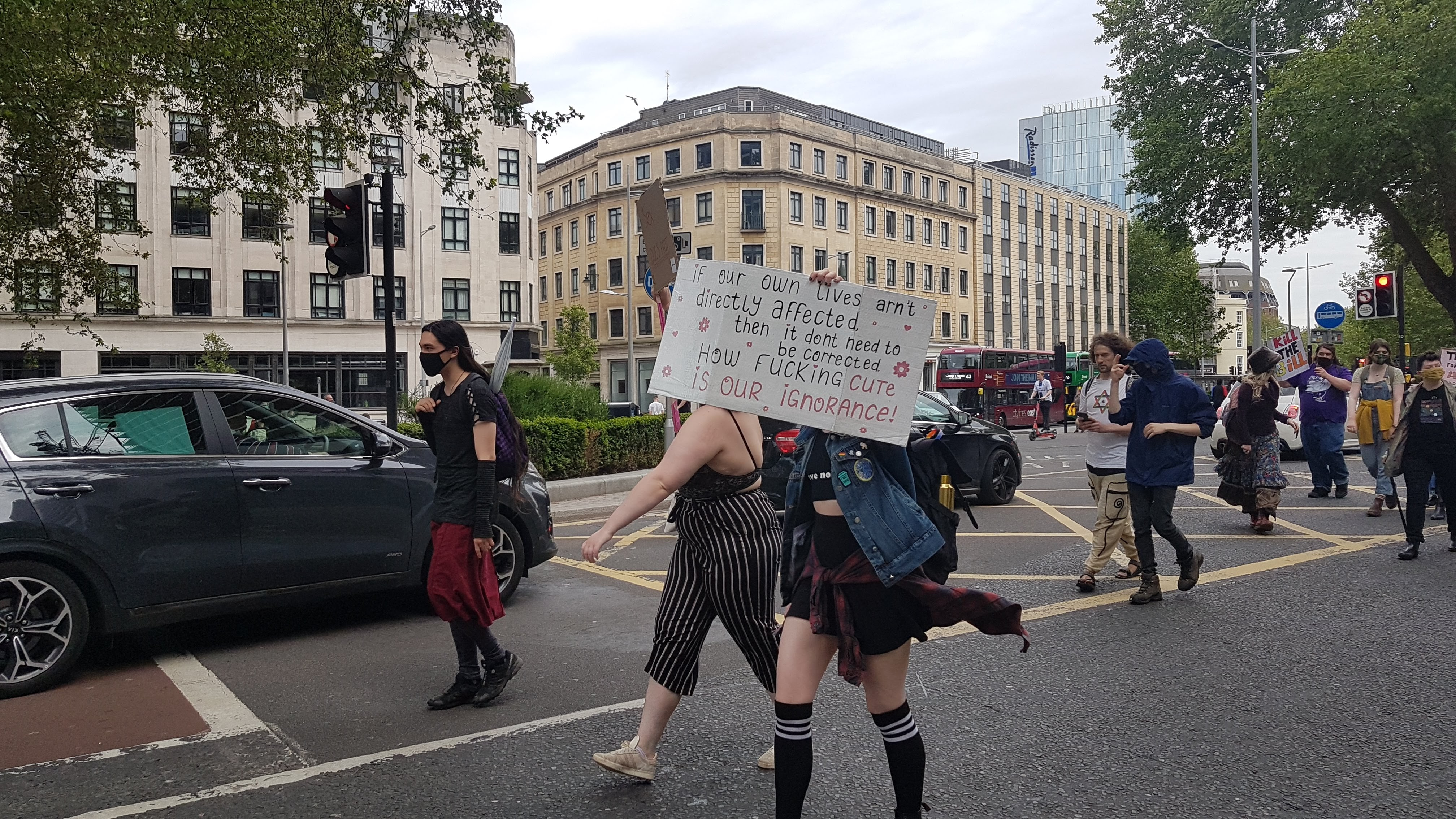 """Protester holds a placard reading """"if our own live aren't strictly affected then it don't need to be corrected. How fucking cute is our ignorance."""""""