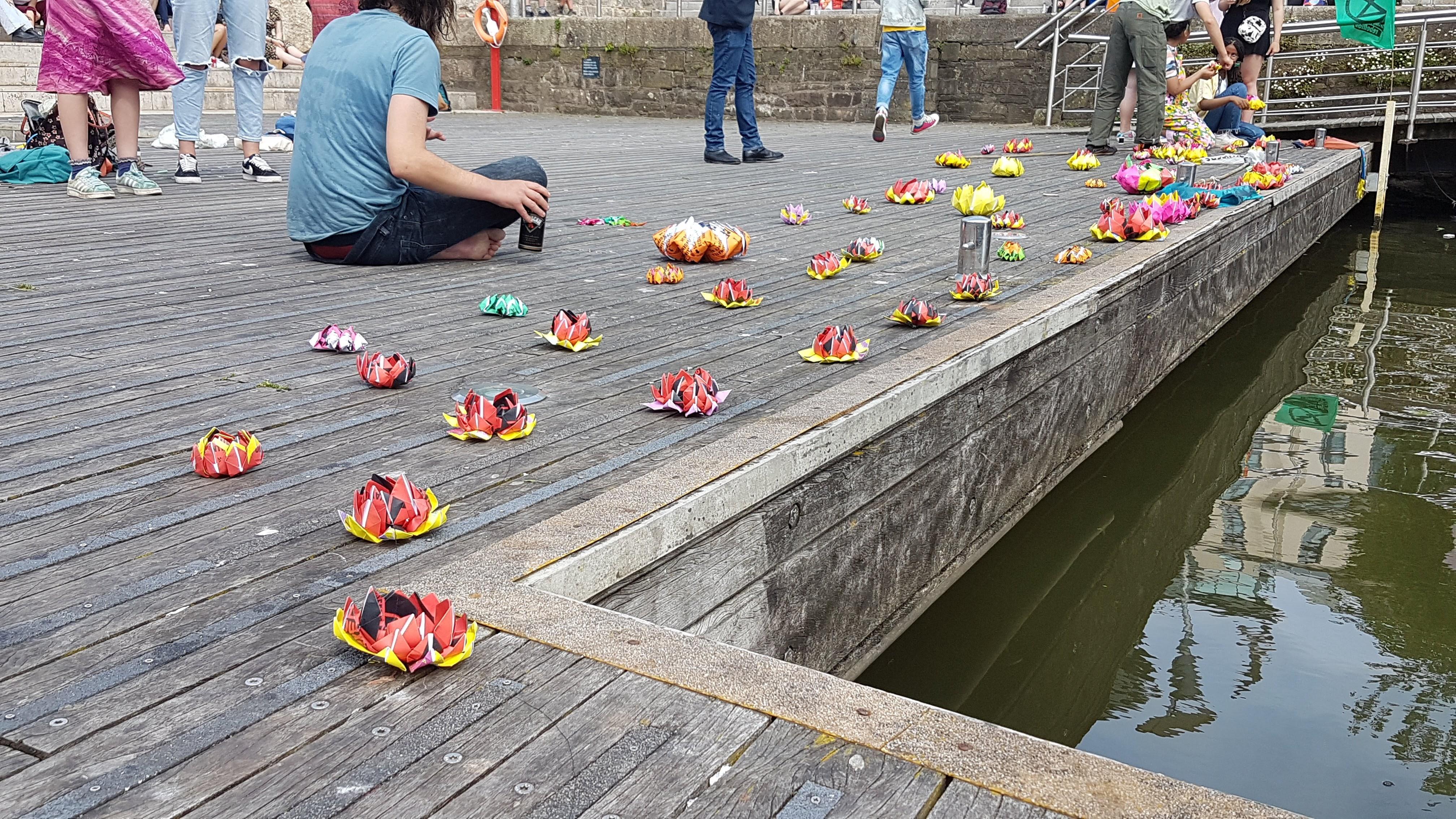 Two dozen origami lotuses arranged along the edge of Bristol Harbour.