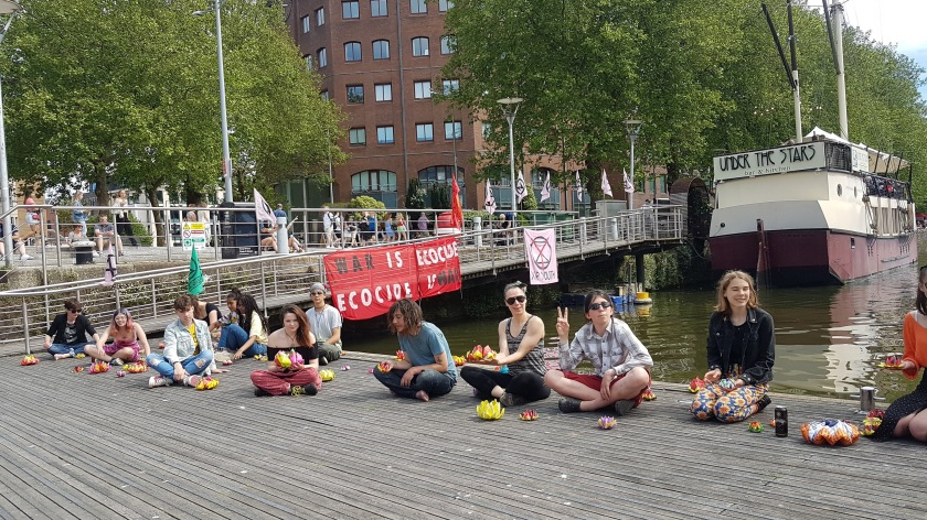 14 activists sat holding origami peace lotuses next to Bristol harbourside.