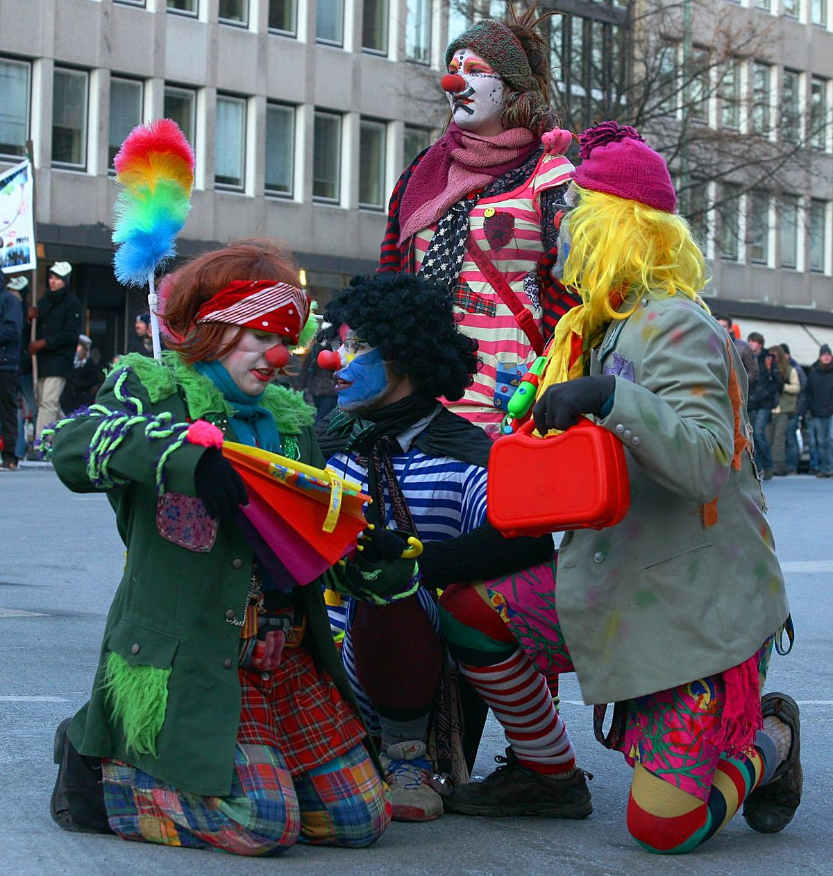 Four clowns kneel and stand on the street at a protest