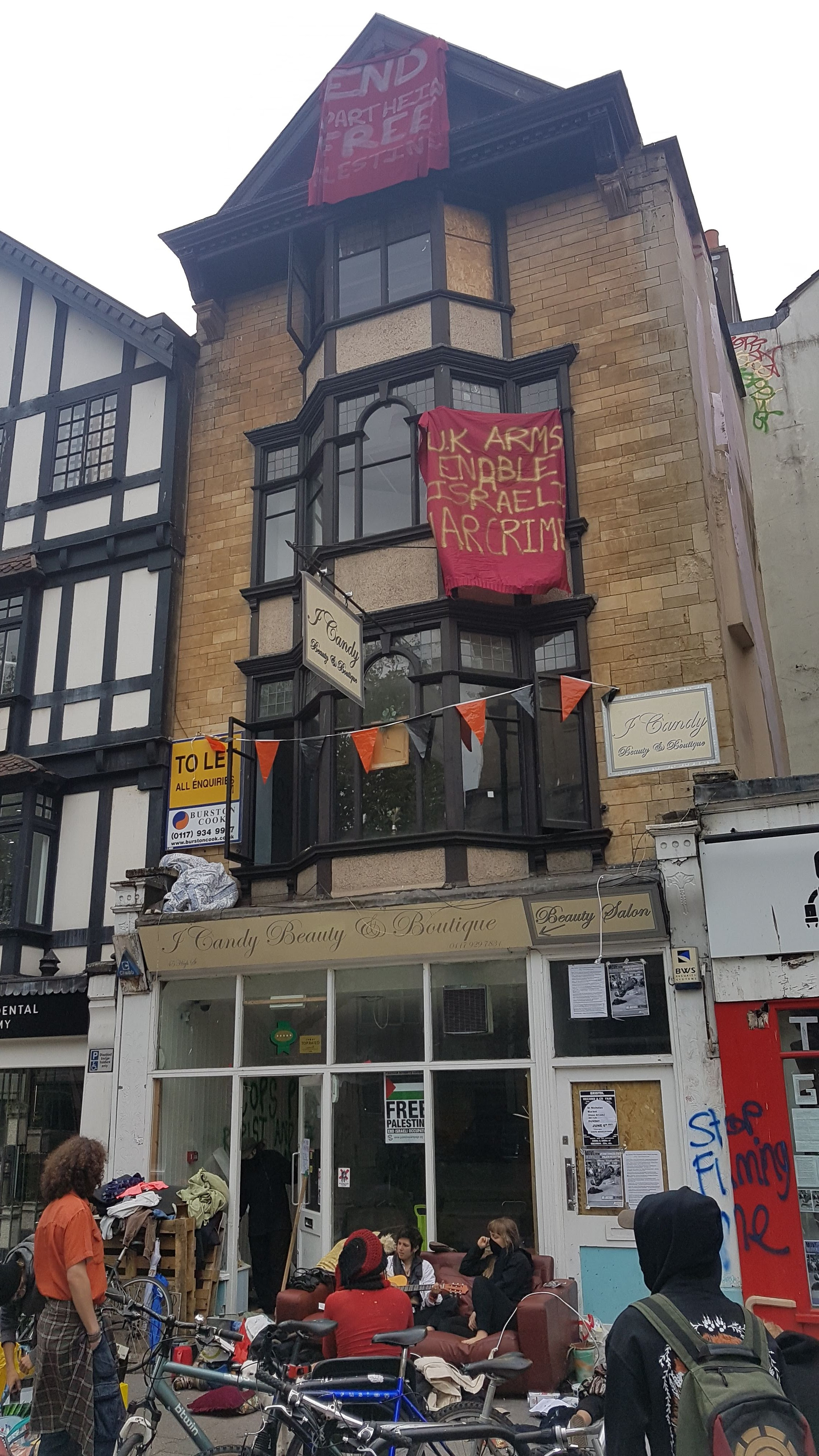 Five-storey building with squatters sat outside. There are banners hanging from the windows.