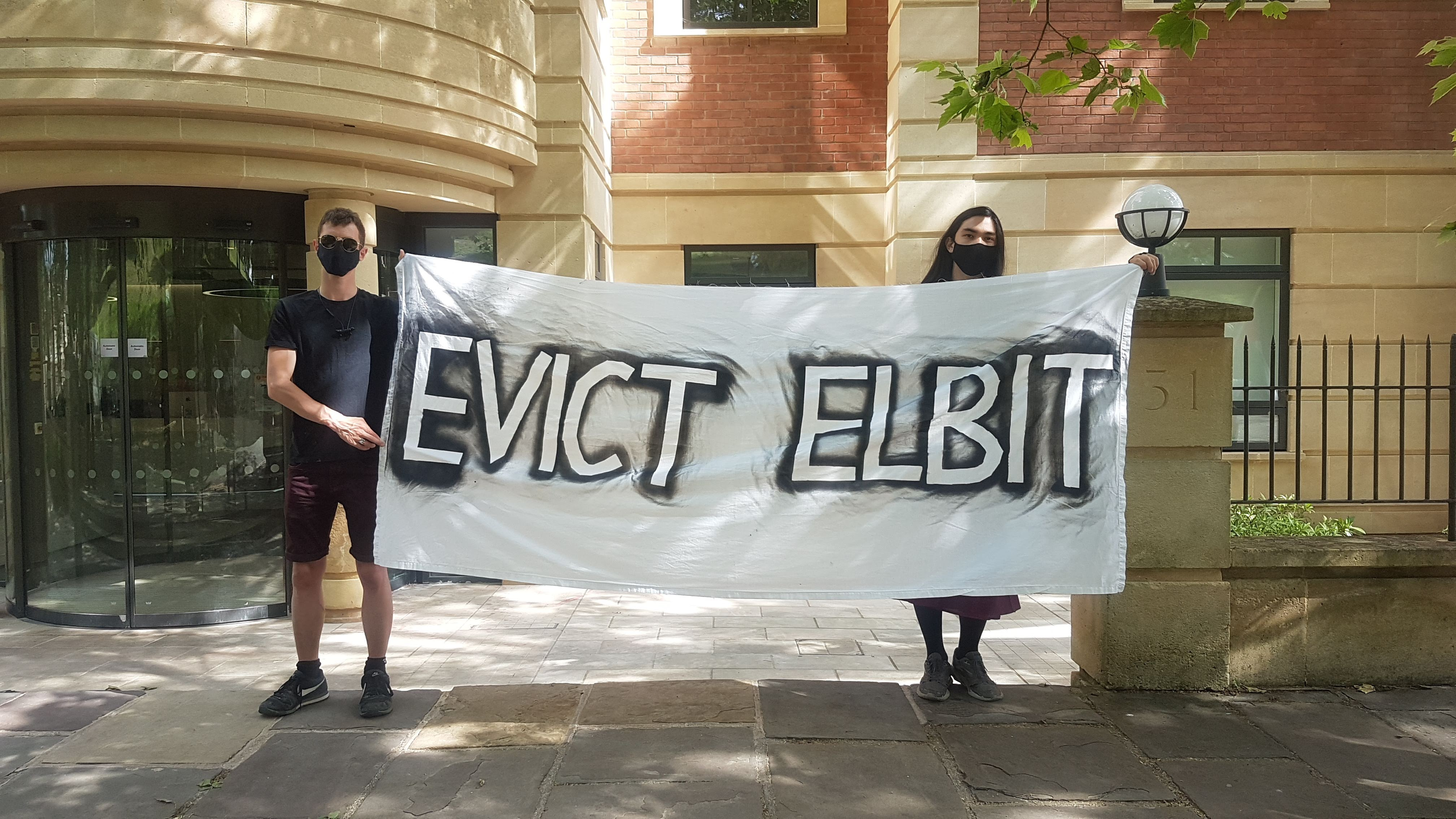 """Two protesters stand either side of a banner that reads """"Evict Elbit"""""""