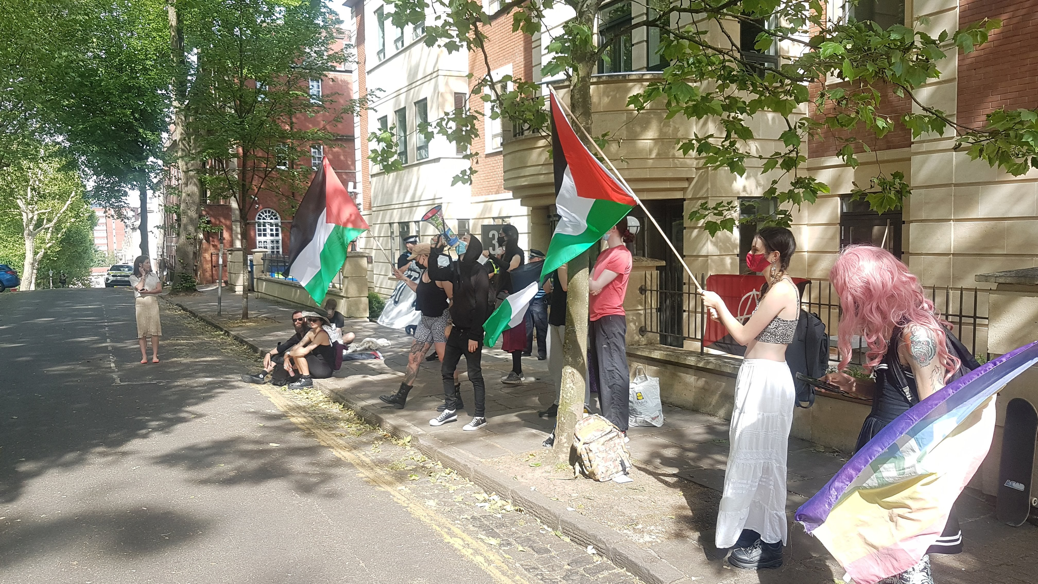 Thirteen protesters outside an office building.