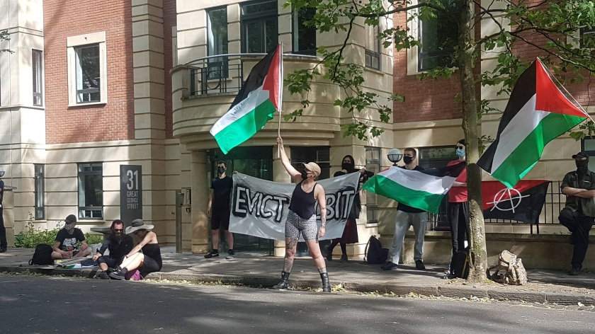 """Nine protesters are visible, carrying Palestine flags and a banner that reads """"Evict Elbit"""""""