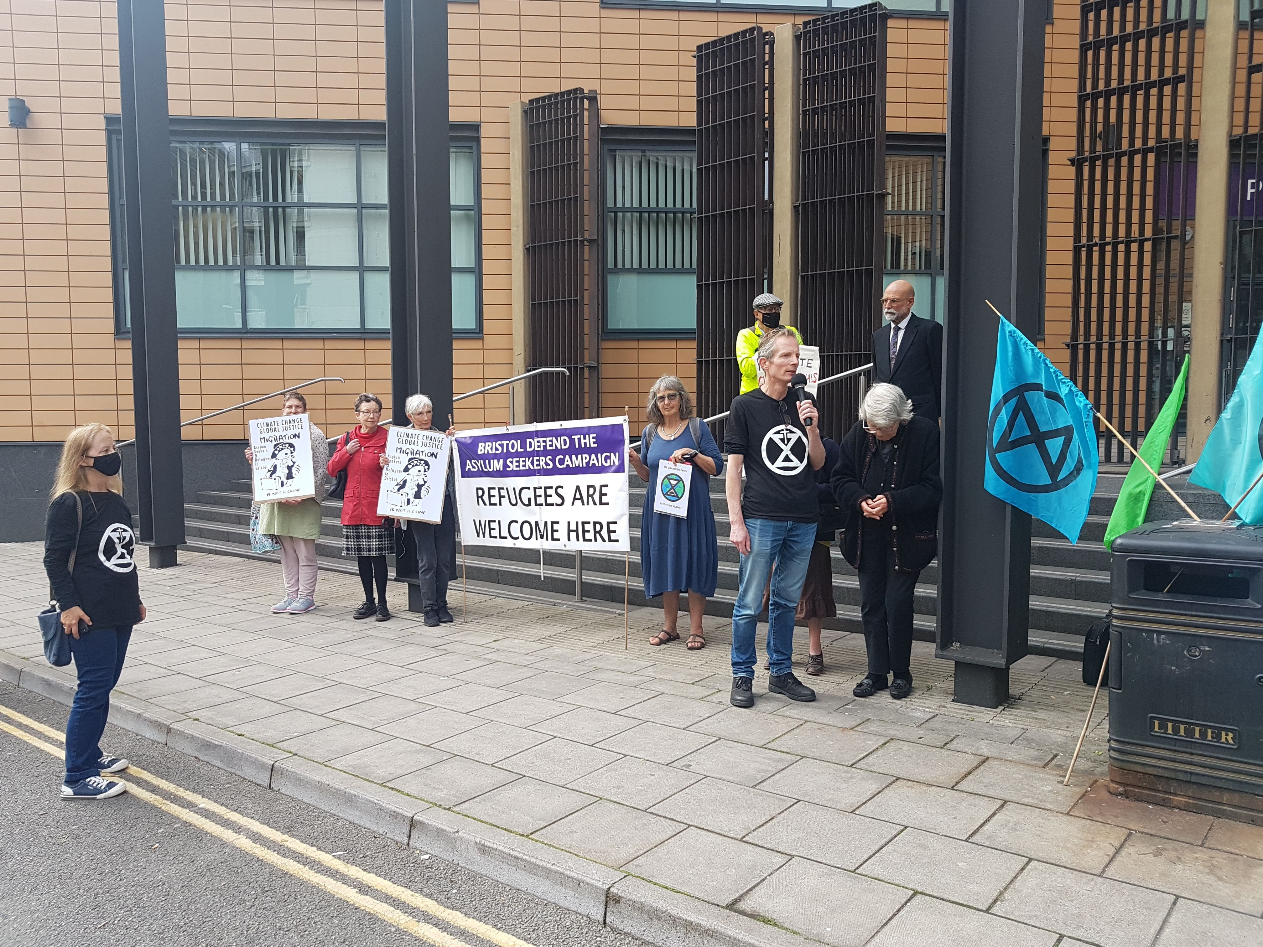 """Sue Parfitt and eight supporters stand outside the courthouse. A banner reads """"Refugees are welcome here"""""""