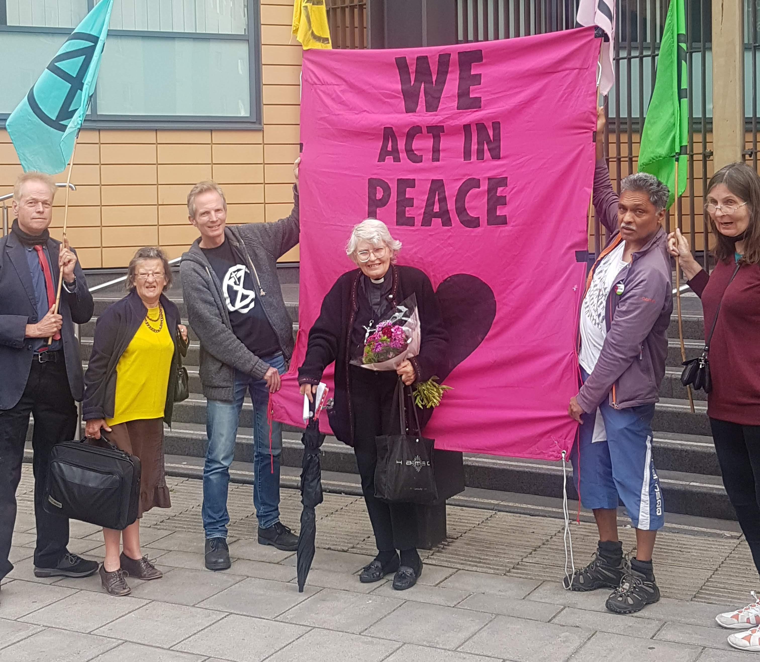 """Sue Parfitt stands in front of a banner that reads """"We act in peace"""""""