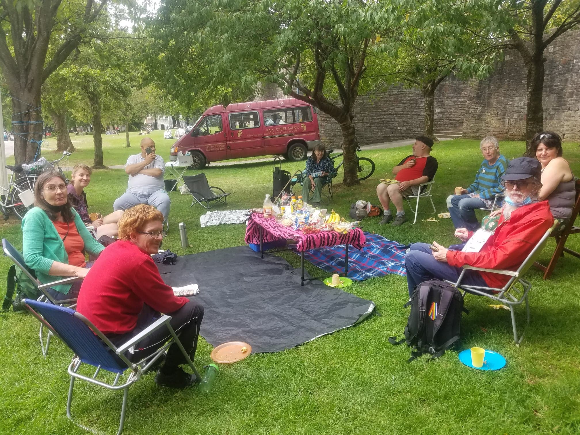 Nine people sit around a picnic blanket and table