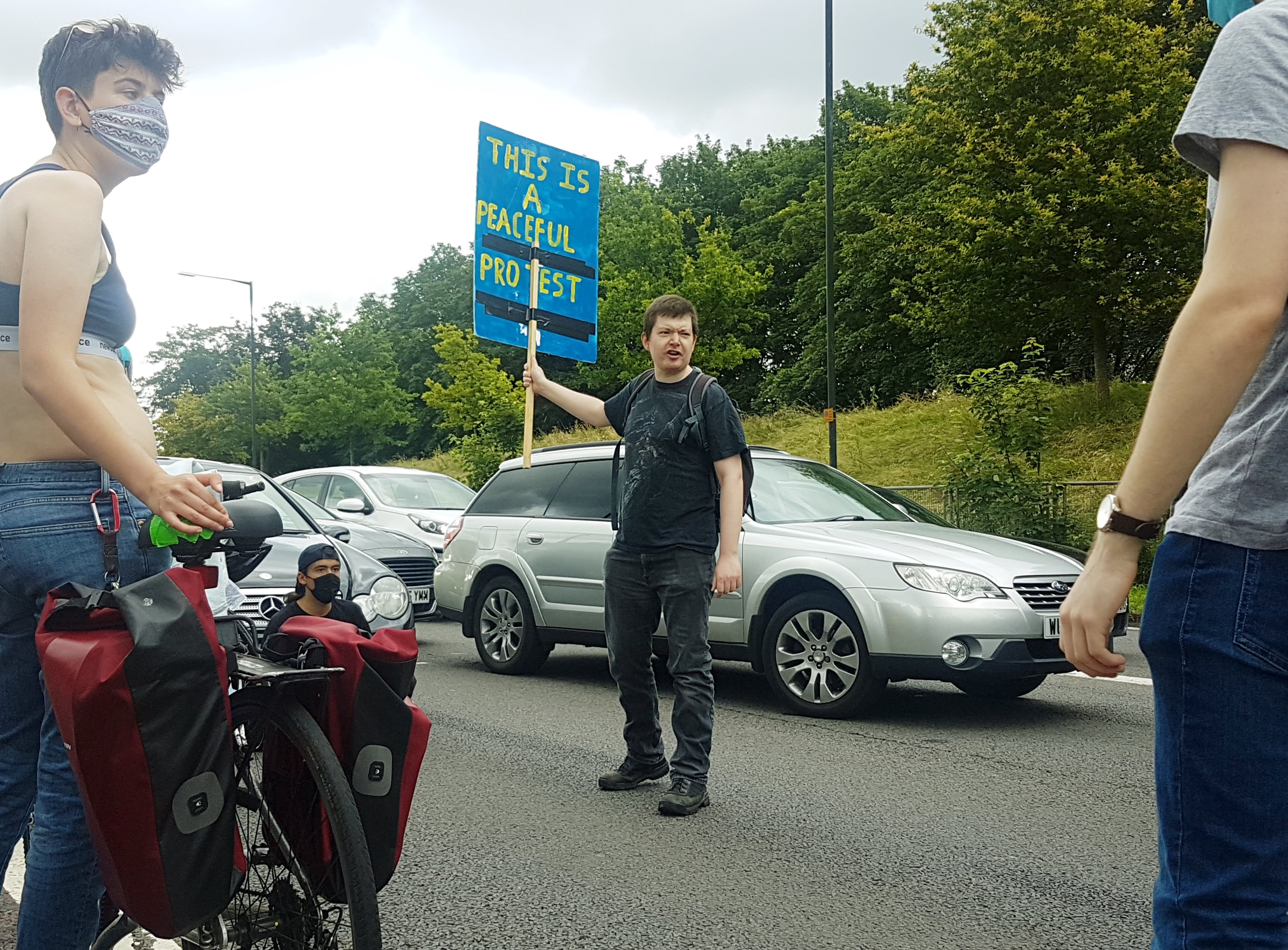 """Kill The Bill on the M32 motorway. A protester stands in front of traffic with a placard reading """"This is a Peaceful Protest""""."""