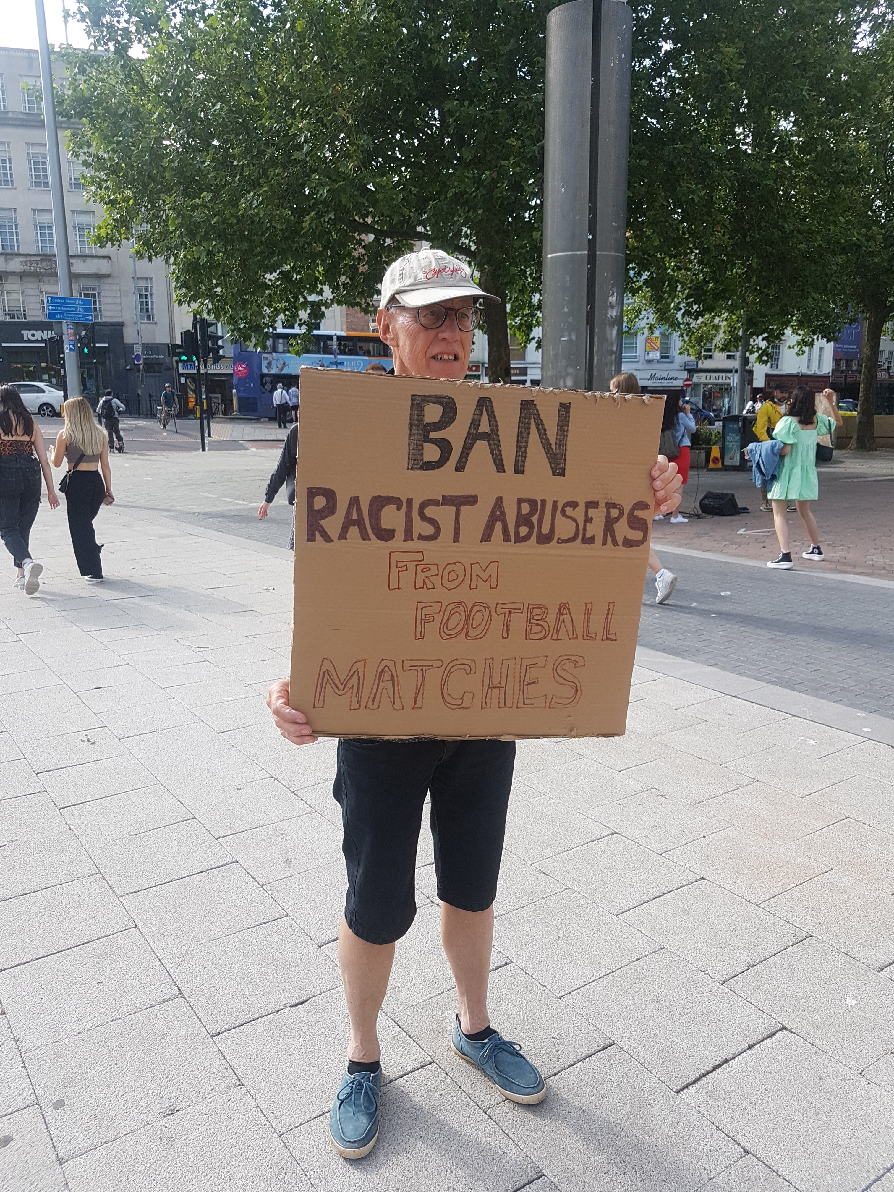 """Man holds a placard saying """"Ban Racist Abusers From Football Matches"""""""
