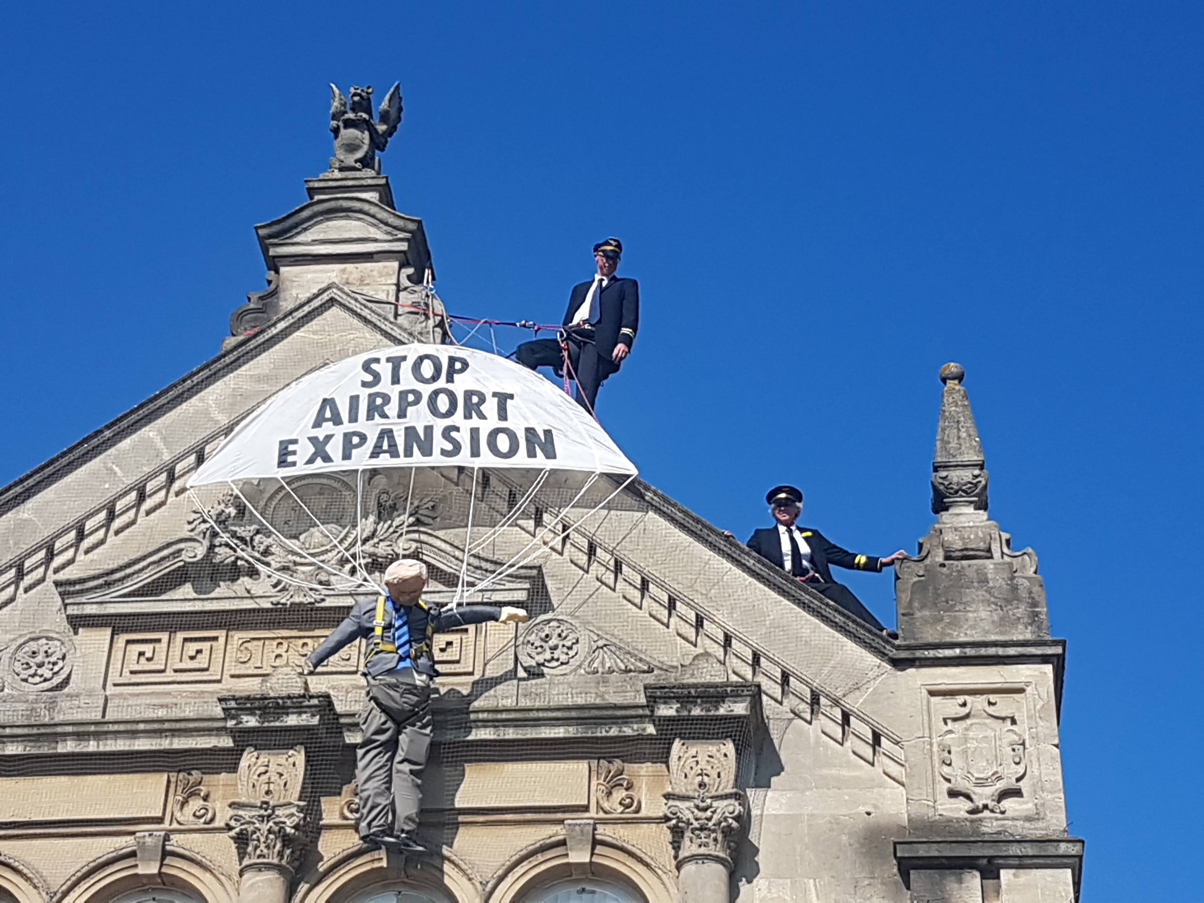 Two people dressed as pilots harnessed on the roof of Weston-super-mare town hall.