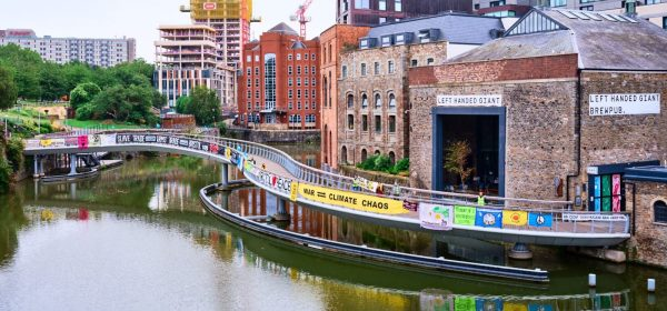 Long bridge over Bristol harbour strung with many banners of different colours.