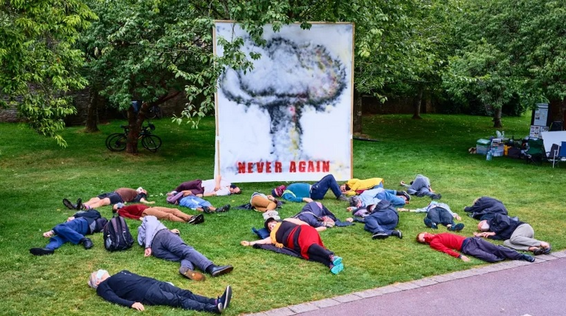 """Twenty demonstrators at a """"die-in"""" lie on the ground in front of a banner bearing an image of a mushroom cloud and the words """"never again"""""""