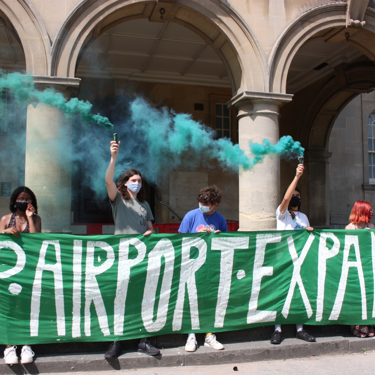 """Seven youth activists hold a banner saying """"Skolstrejt For Klimatet"""" outside Weston-Super-Mare town hall. Two hold smoke bombs releasing blue smoke."""