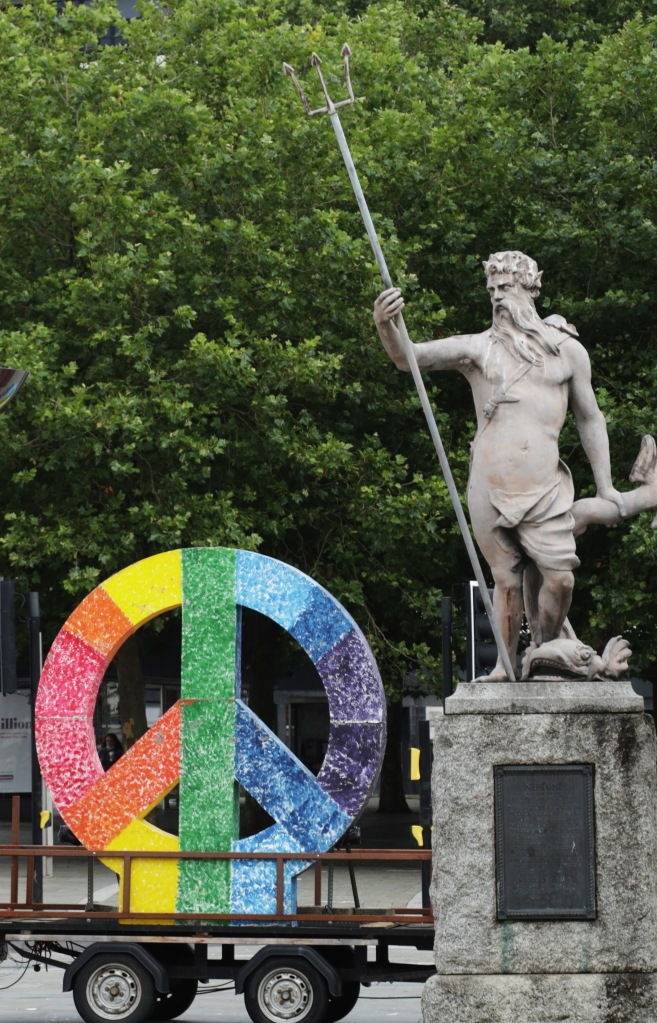 Rainbow-coloured peace symbol stands next to a statue of Neptune.