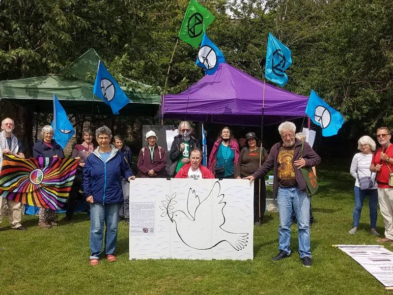 Thirteen protesters stand around a petition shaped like a dove. They are holding flags with peace symbols on them.