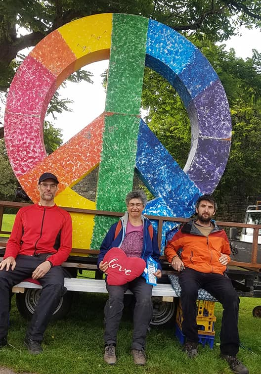 A peace symbol, painted in rainbow colours. Three people, a man, a woman and another man, are seated in front of it, smiling at the camera.