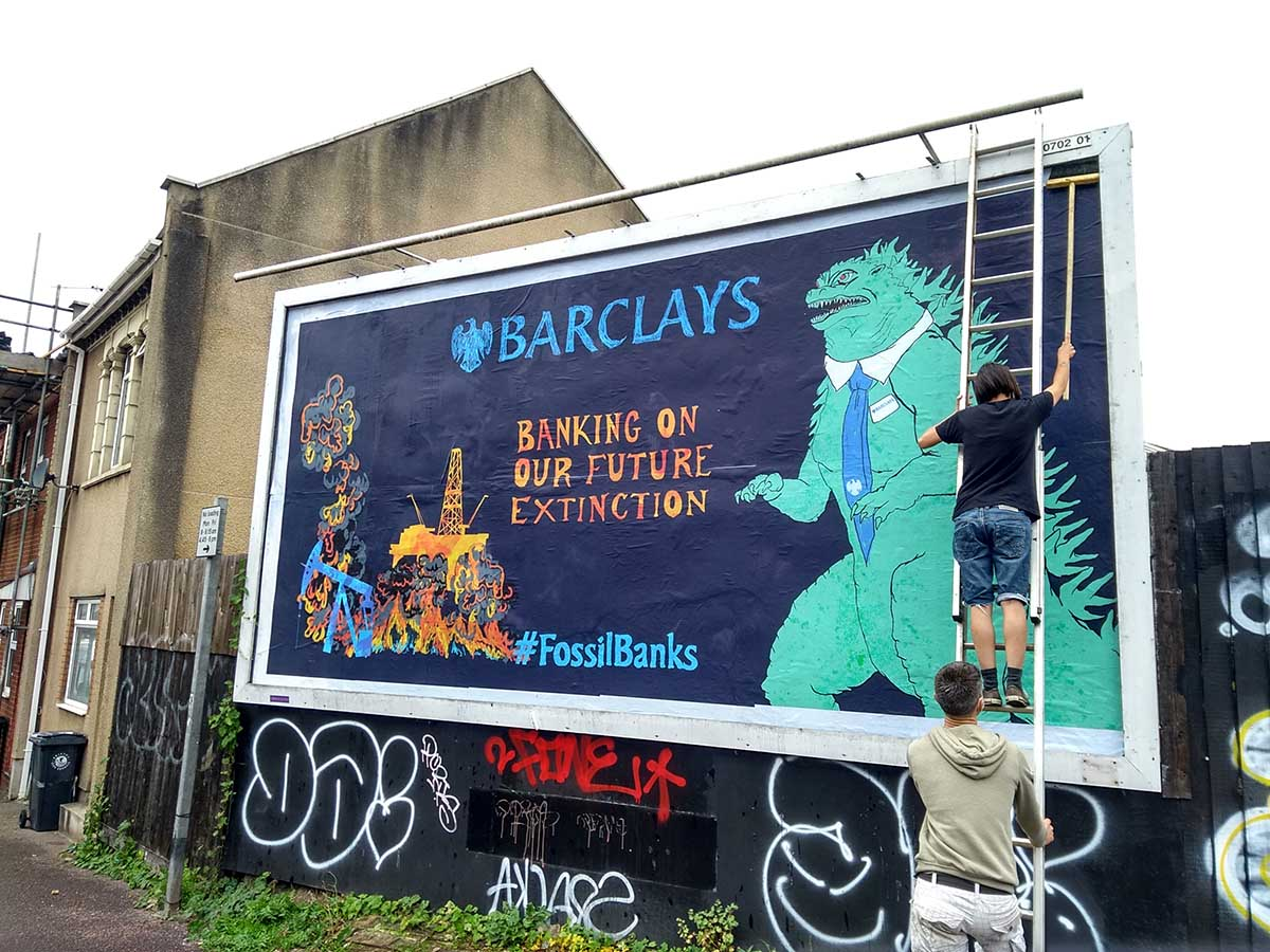 """Billboard showing a cartoon dinosaur and the caption: """"Barclays: Banking on our future extinction"""""""