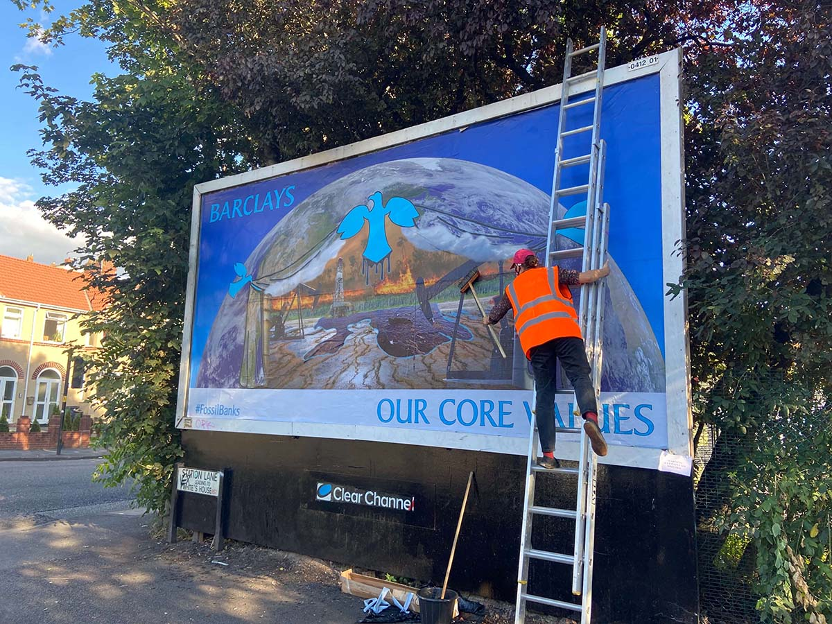 """Billboard being installed by a man on a ladder. The poster shows scenes of fossil fuel extraction and a burning planet with the caption: """"Barclays: Our Core Values"""""""