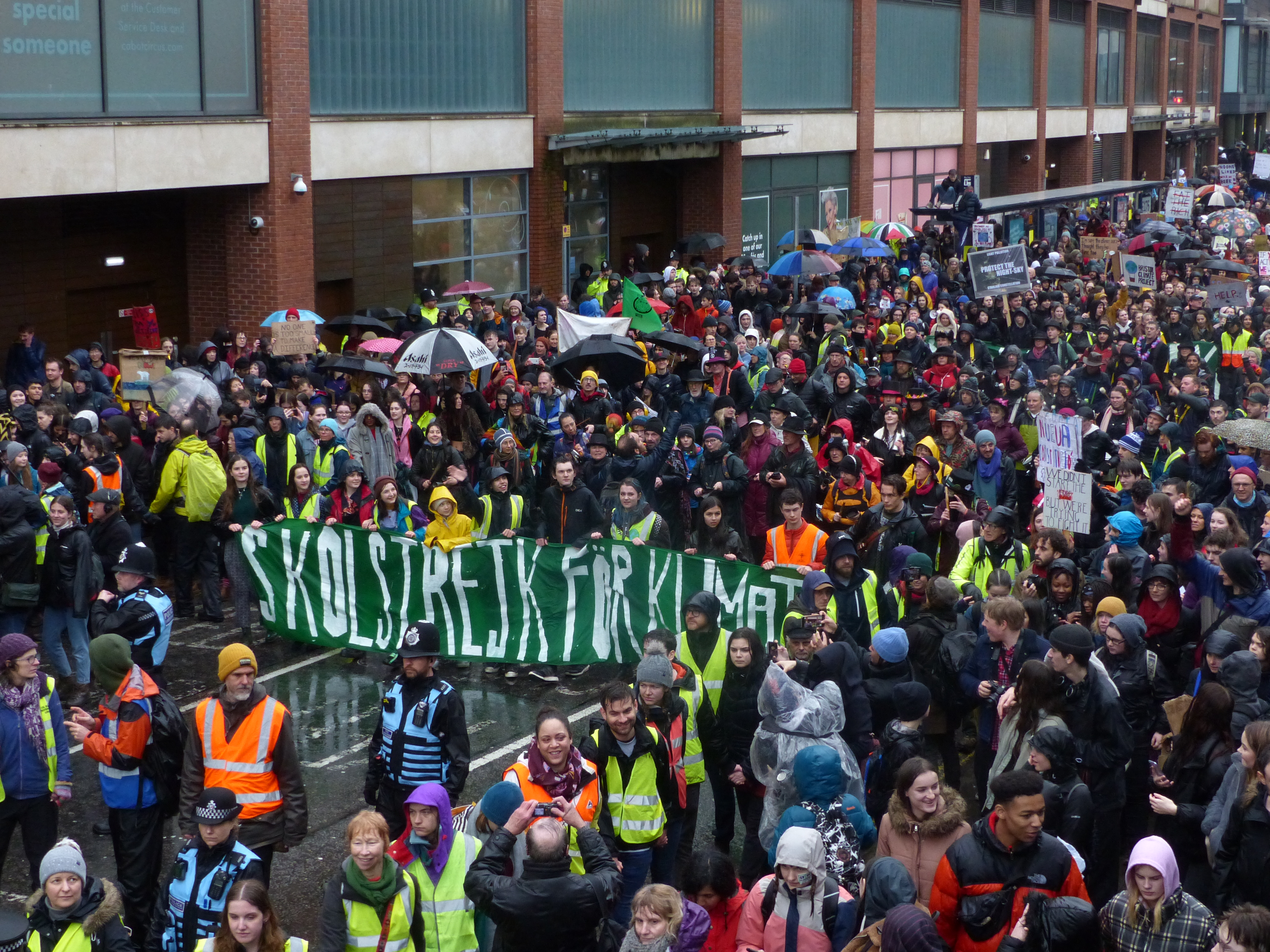 """Long range photo of many hundreds of people marching through Bristol. At their head, a banner bearing the words: """"Skolstrejk For Klimatet"""" as per Greta Thunbergs School Strike for Climate."""