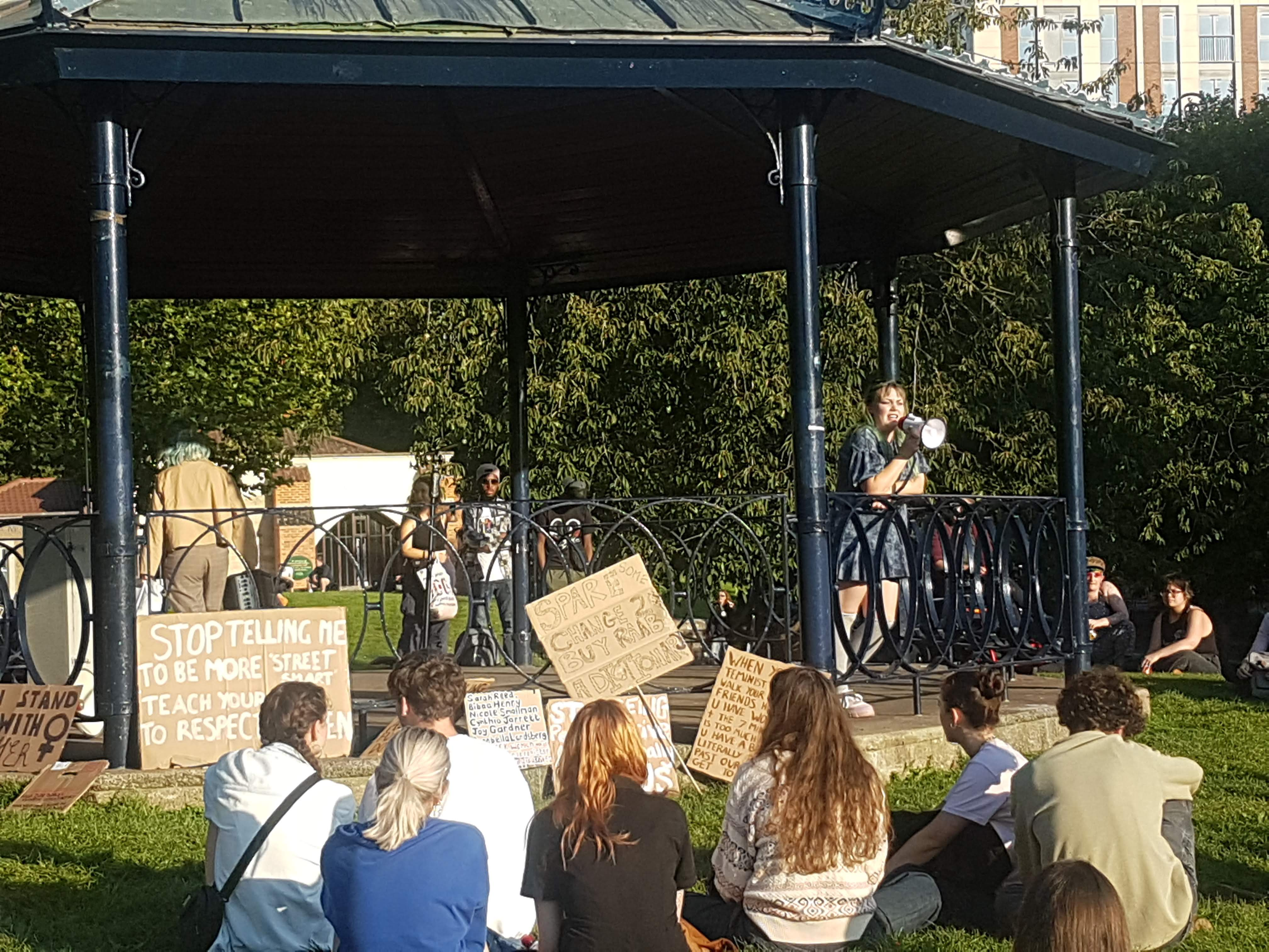 A woman speaks through a megaphone to the crowd at the Bandstand.