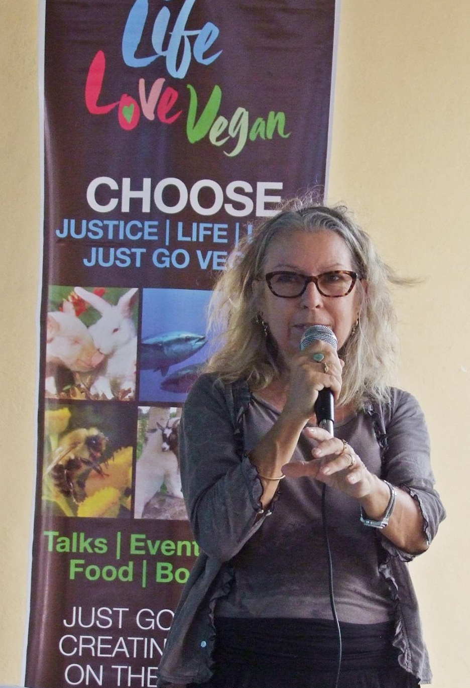 """Pamela stands with a microphone, facing the camera. A banner behind reads """"Life Love Vegan"""""""