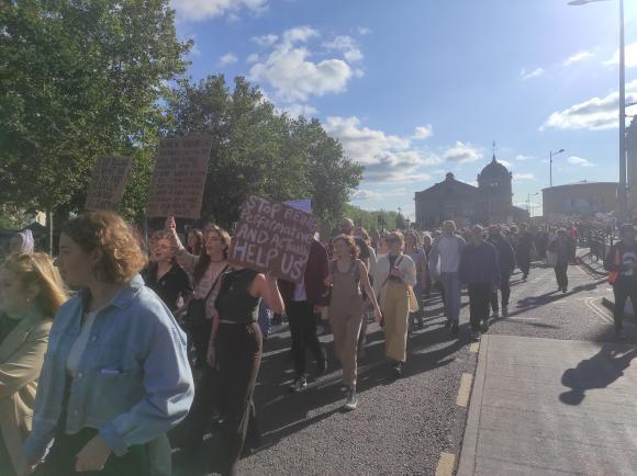 Large crowd marching on a road in Bristol.