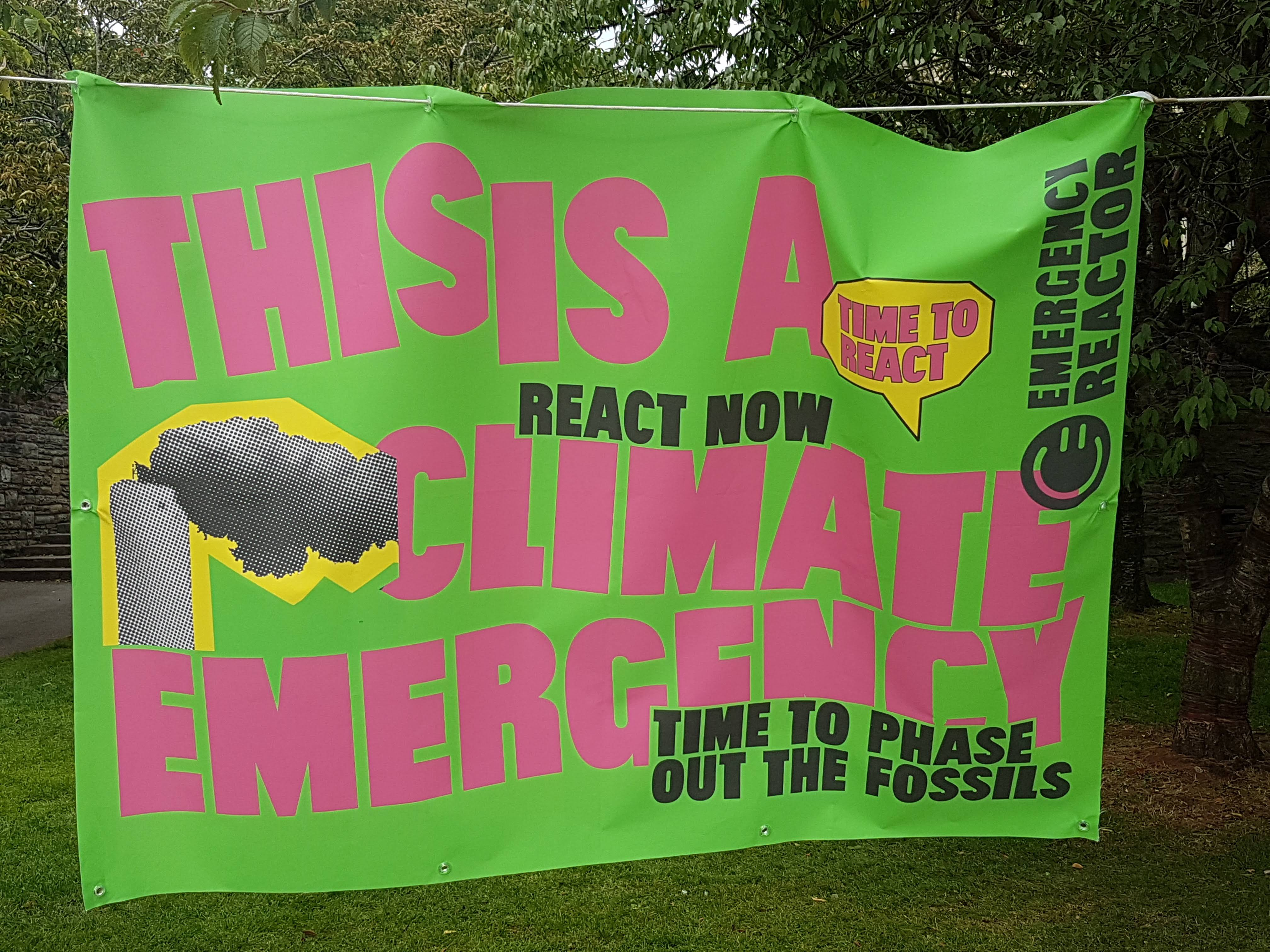 """Banner reads """"this is a climate Emergency. React Now. Time to Phase Out Fossil Fuels"""""""